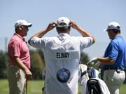 Caddie and Evans Scholar Grant Cassle, center, with John Elway and John Lynch before the BMW Championship exhibition.