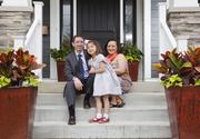 David and Thuy Smith, along with their daughter Cameron, pose in front of their new, energy-efficient home.