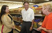 """From left, Lisa Garcia-Mitchell, advertising manager for Don Quiote, Herb Gukushima, senior vice president talking with Foodbank volunteer Gloria Gerber at the 19th Annual """"Check-out Hunger"""" Program at the Hawaii Foodbank's warehouse located at 2611 Kilihua St."""
