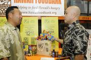 """Carl Fukushima, right, manager of district operations for Safeway Hawaii, and Gerald Shintaku, customer business lead for Kraft Foods, organize donated canned food for Hawaii Foodbank's """"Check-Out Hunger"""" program at The Hawaii Foodbank's warehouse in Honolulu."""