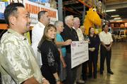 Sweetie Pacarro, spokeswoman for Kraft Foods in Hawaii, smiles as executives gather for a check presentation for the Hawaii Foodbank in the amount of $236,045.06