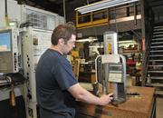 Cody Barton, 19, measures a part at PEMS. Barton was hired out of high school, and he runs computer-controlled machines that make parts for the Remington Arms factory in Ilion, 10 miles west.