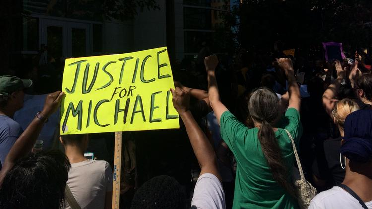 "A ""Justice for Michael"" sign at a Clayton protest Aug. 11 of the shooting of 18-year-old Michael Brown."