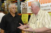 """Bob Stout, left, president of Times Supermarkets, talks with Hawaii Foodbank President Dick Grimm at the foodbank's annual """"Check-Out Hunger"""" program at its Honolulu headquarters."""