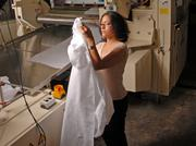 A researcher with The Nonwovens Institute tests a piece of fabric manufactured on equipment kept at N.C. State University's Centennial Campus.
