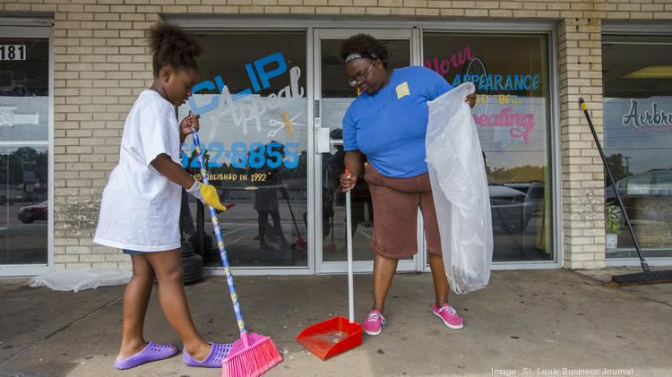 Tina Tramble ¨ and her eight-year old daughter Natayvia clean up trash outside some businesses on W. Florissant Ave. on Aug. 18.