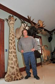Peter Stone, owner of PEMS, at home with some of the taxidermied animals from his hunting trips. He is planning a hunting trip to Wyoming this fall with his son.