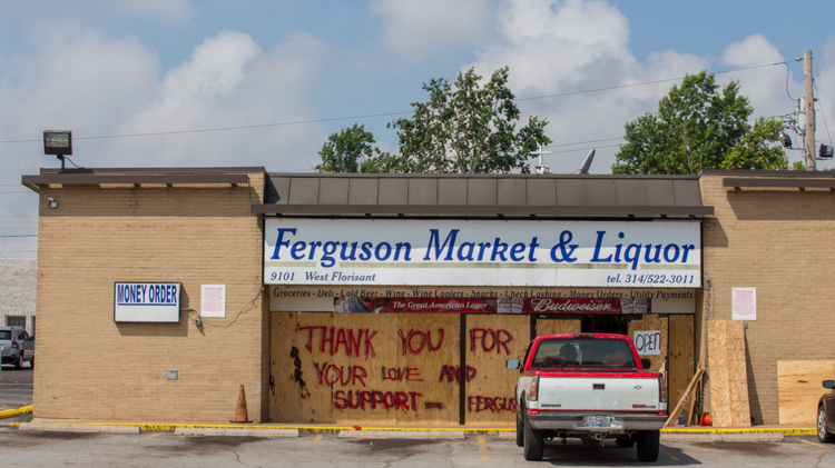 """Written on the boarded-up windows of Ferguson Market & Liquor: """"Thank you for your love and support—Ferguson."""""""