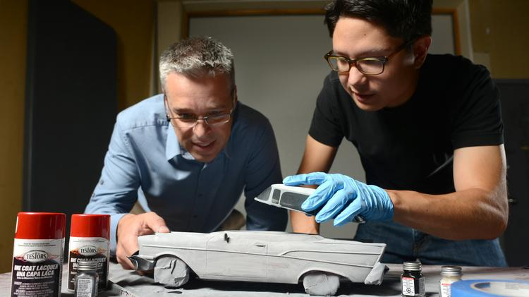 Pete Saari (left) and Noah Miwa fit together an urn that will look like a collectable car. From here, the car will be sanded and painted.