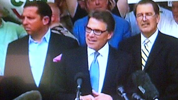Rick Perry and some of his lawyers on the courthouse steps after being booked on abuse of office charges.