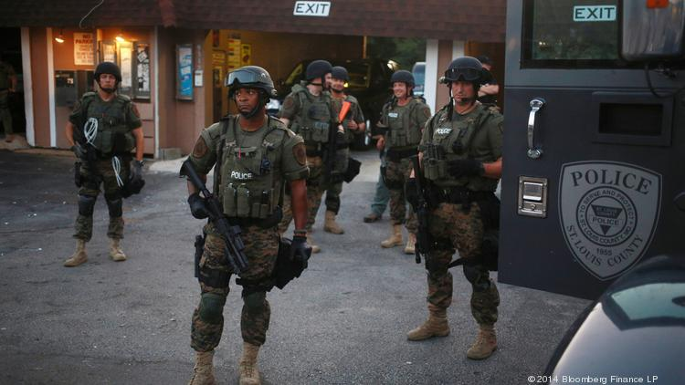 Armed officers from the St. Louis County Police stand alongside their truck as they monitor demonstrations in Ferguson on Tuesday, Aug. 19.