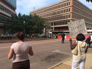 A protestor with a sign calling for McCulloch's removal from Mike Brown proceedings.