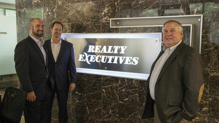 Jeff Hawke, far left, and Joel Moyes of Kinetic with Jeff Murtaugh of Realty Executives.