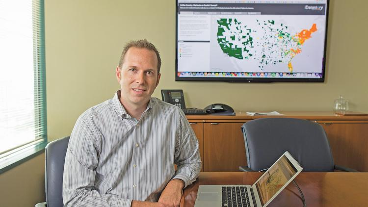 Matt Felton of Datastory LLC explains a map displaying the distribution of Starbucks and Dunkin Donuts across the country.