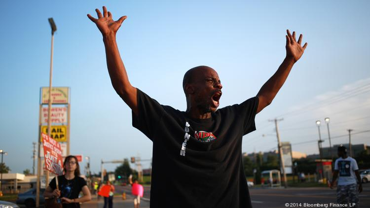 A protestor is seen standing with his arms raised above his head during demonstrations in Ferguson, Missouri, on Wednesday, Aug. 20.