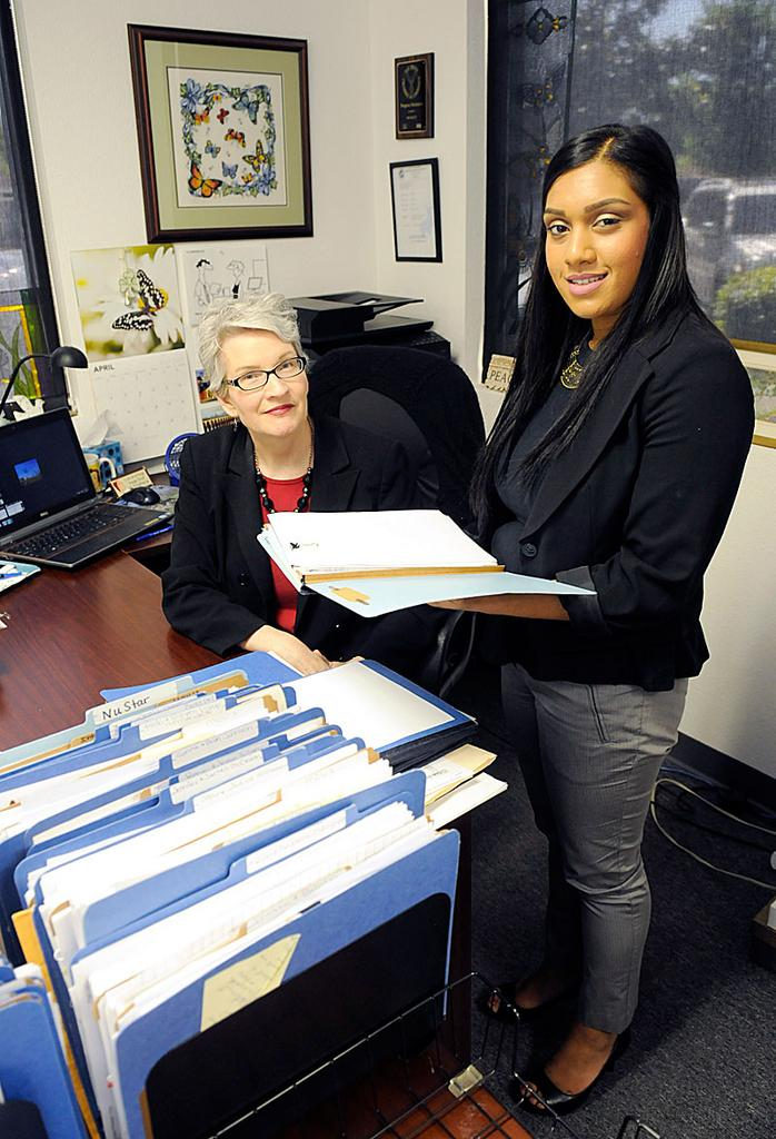 When mediating workplace conflicts, Nancy Milton, left, with administrative assistant Ronita Kumar, employs three-party discussions that focus on finding the root of the problem.