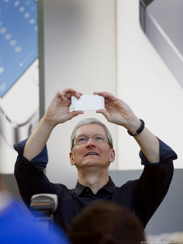Tim Cook, chief executive officer of Apple Inc., takes a photograph during the launch of the iPhone 5c and 5s.