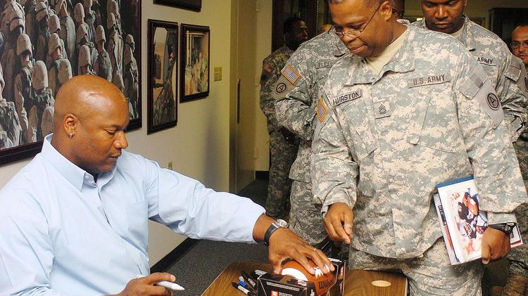Former football and baseball star Bo Jackson signs autographs for U.S. soldiers in Georgia. Jackson is in legal fight with a Scottsdale food company.