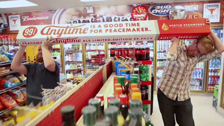 Two Austin Beerworks staffers struggle to hoist the brewery's massive 99-pack of Peacemaker Ale through a convenience store in this image from a company video promoting the massively-sized case of beer.