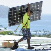 Aaron Paahana, a photovoltaic installer for Hawaii Energy Connection, carries PV panels on a Honolulu rooftop. Solar energy remains one of Hawaii's fastest-growing industries.