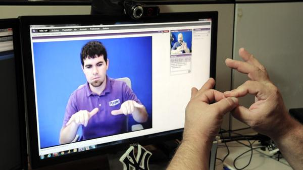A Purple Communications technician demonstrates the company's video relay service for the deaf. The company says its new SmartVP 2.0 videophone connects the deaf user via streaming video with a American Sign Language interpreter.