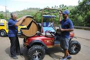Nohokai Production Services General Manager Brian Barboza, left, opens a custom-built wooden-barrel bar attached to the back of a golf cart, which also was custom-built for a Dewar's Scotch Whisky promotion. Looking on is Nohokai founder Curtis Colin, who is preparing to open a showroom to market his golf carts. He also plans to increase his staff to focus on sales and service.