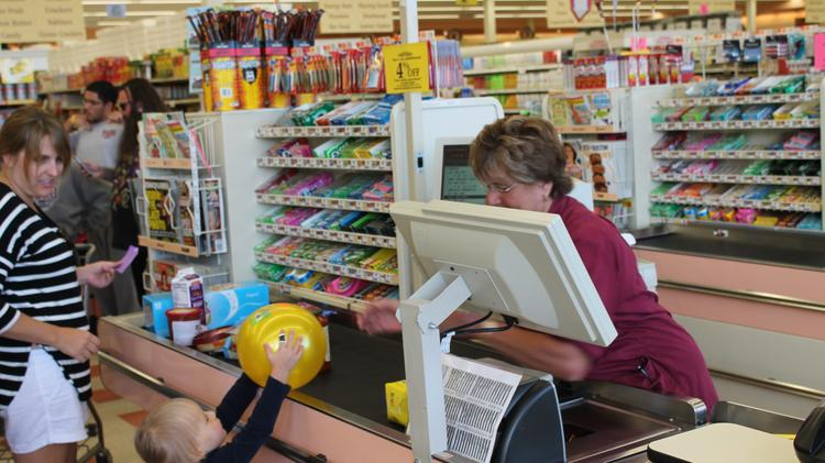 Cashier Joanne Interrante hands a newly purchased ball to customer Margaret at the Gloucester store the morning of Aug. 28, 2014, after ousted CEO Arthur T. Demoulas resumed control of the company.