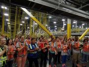 Newly hired Amazon employees celebrate the first shipment from Amazon's Lakeland fulfillment center.
