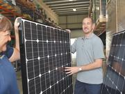 Sunetric President Aaron Kirk and warehouse manager Bonnie Allen perform a quality control check on their supply of solar panels.