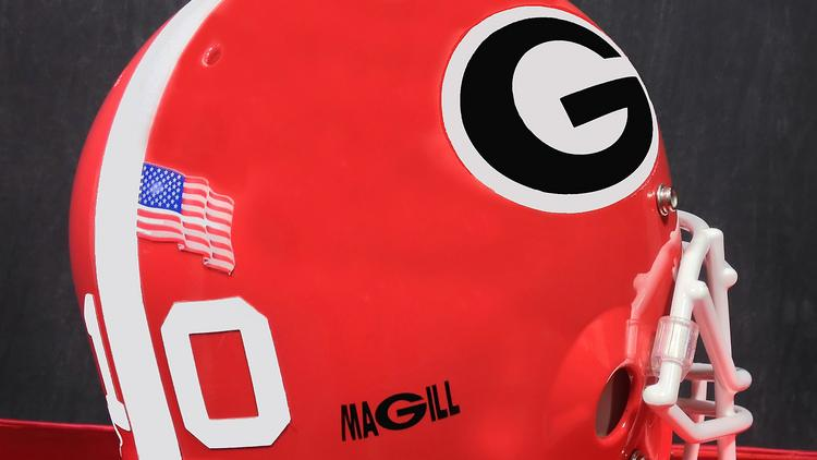 "The decal, which will be worn on the team's helmets, spells ""MAGILL"" with the Georgia power ""G"" used in the lettering."