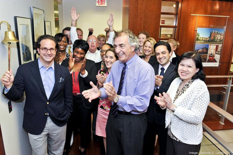 """Toby Bozzuto, left, rings a """"bell of accomplishment"""" used when the company celebrates major milestones as his father, Tom, and  employees look on."""