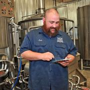 Branchline Brewing is an alpha tester for the Monk's Toolbox process of collecting data. Les Locke is pictured using an iPad to monitor inventory and production data.
