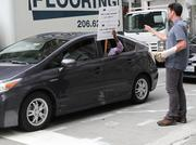 A passerby confronts one of about two dozen Uber drivers honking their horns in a convoy encircling downtown Seattle while another two-dozen picketed while protesting around Smith Tower on Aug. 29.