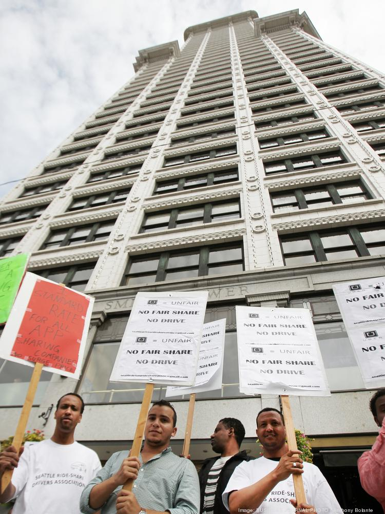 About two-dozen Uber drivers picket while another two-dozen drivers drive honking their horns in a convoy encircling Smith Tower in downtown Seattle on Aug. 29. Drivers were protesting wage cuts.