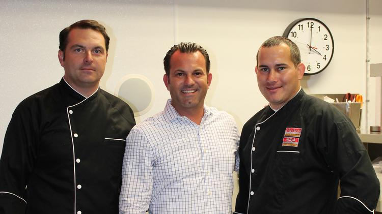 Chef Tom Smith (left); Ryan Joy, senior director of research and development & culinary; chef Joe Parker, gathered in the Checkers test kitchen.