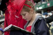 An unidentified girl studied the racing form prior to the big race.