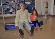 Martin Taplin shows off a swing sculpture with his grandaughter Chloe Fuller, age 4, in the lobby of the Sagamore.