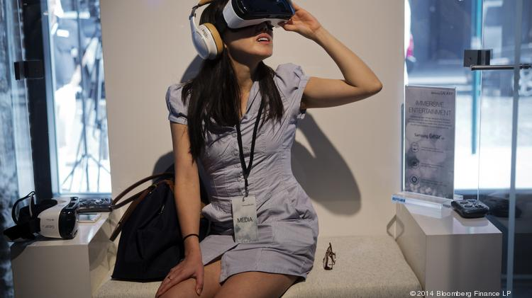 A member of the media tries out a virtual-reality headset during a Samsung Electronics Co. product release event in New York, U.S., on Wednesday, Sept. 3, 2014. Samsung Electronics Co. unveiled a pair of Galaxy Note smartphones, including one with a display extending down the side, as the No. 1 seller tries to fend off Apple Inc.'s push into large-screen devices. The company also showed off a virtual-reality headset, developed with Facebook Inc.'s Oculus unit, and a new smartwatch.  Click through to begin slideshow.