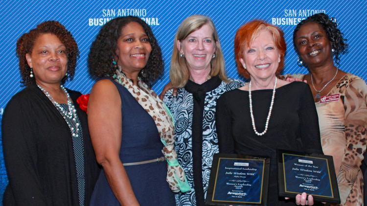 Julie Wisdom Wild, CEO of Alpha Home, with the two plaques honoring her role as a woman leader. She is joined by members of the organization.