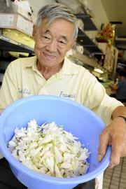 Francis Wong, owner of Jenny's Leis & Flowers, shows a bucket of cleaned tuberose ready to be strung into lei.