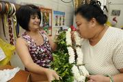 Neli Gabbuat of Lita's Leis & Flower Shop allows customer Chandra Satele, right, to smell a fragrant double tuberose lei with red rose buds with a Hilo maile lei before boxing it up for an out-of-state graduation.