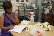 Fely Magallanes, lei maker for Lita's Leis & Flower Shop in Honolulu, takes an order from a customer while stringing lei.