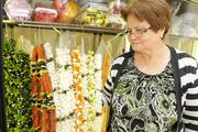 Lourdes Floures, lei maker for Pauahi Leis & Flowers, shows a selection of fresh flower lei of tuberose with rose buds and lantern Ilima as well as cigar lei with kukui nut.