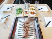 Steak from grass-fed, Washington state beef cooks atop a traditional Korean tabletop grill at Chef Rachel Yang's new eatery Trove located on Capitol Hill in Seattle.