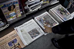 A customer picks up a copy of the New York Post at a news stand in New York, U.S., on Wednesday, Nov. 11, 2009.
