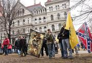 Protestors begin gathering before the gun-rights rally. Confederate flags were present, as well as the yellow Gadsden Flag, which has become an adopted symbol of the Tea Party movement.