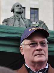 Tom King, president of the New York State Rifle and Pistol Association. Behind him is a statue of George Washington.
