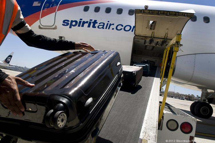 A ground crew member loads baggage onto a Spirit Airlines Inc. plane at the San Diego International Airport in San Diego.