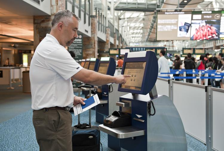 A traveler uses an automated border clearance self-service kiosk at Vancouver International Airport.