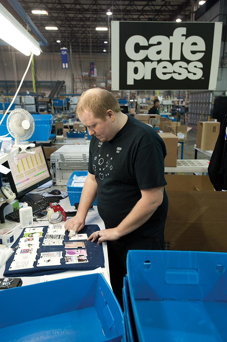 A CafePress workers cleans each freshly printed iPod cover in preparation for shipping.